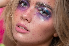 Paint splash, metallic gold and irridescent purple and pink tones on model Mia's makeup