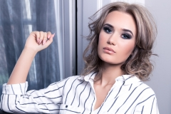 Dramatic eye makeup and glossy lips on model Ella for photoshoot at Acklam Hall
