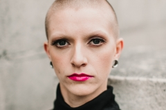 Female model with shaved head wearing a smokey eye look and a bold pink lip colour