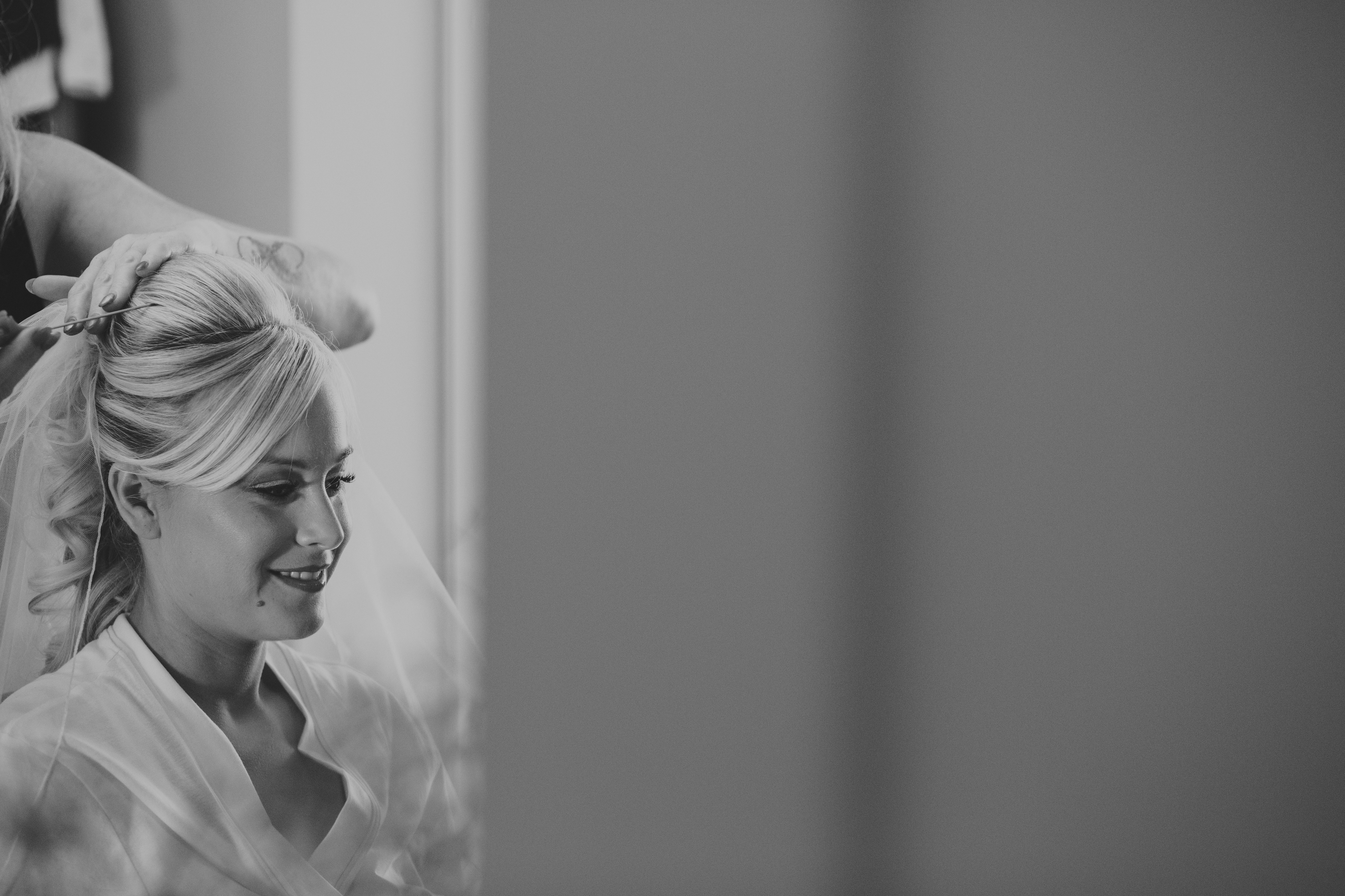 Bride Hannah getting the finishing touches done to her hair and makeup before her wedding at Wrays Barn, Great Ayton.