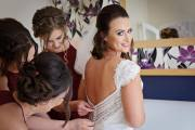 Becca's bridal party helping her fasten her dress before her wedding at Grinkle Park
