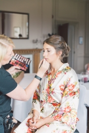 Bride Helen getting her makeup done by Gemma Rimmington on the wedding morning at Grinkle Park, North Yorkshire.