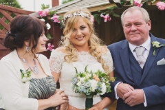 Bride Steph looks beautiful, stood between the mother of the bride and the father of the bride. Wedding reception at The Lordstones, North Yorkshire. Makeup by Gemma Rimmington.