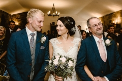 Photo of boho bride with groom and father of the bride. Wedding venue is Danby Castle in North Yorkshire. Makeup by Gemma Rimmington and hair by Dream Hairstyling and Beauty.