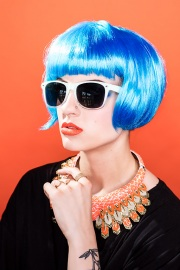 Blue hair, sunglasses, orange lips and orange background.  Editorial makeup.