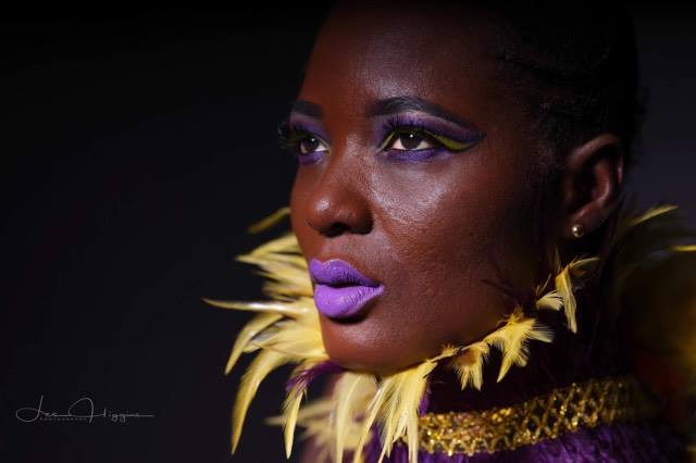 Black model Ayisha close up portrait photo wearing yellow and purple makeup and matching feather collar created by Gemma Rimmington.