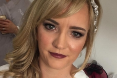 Bride steph is wearing a flawless foundation, dark berry lipstick and a defined eye makeup.