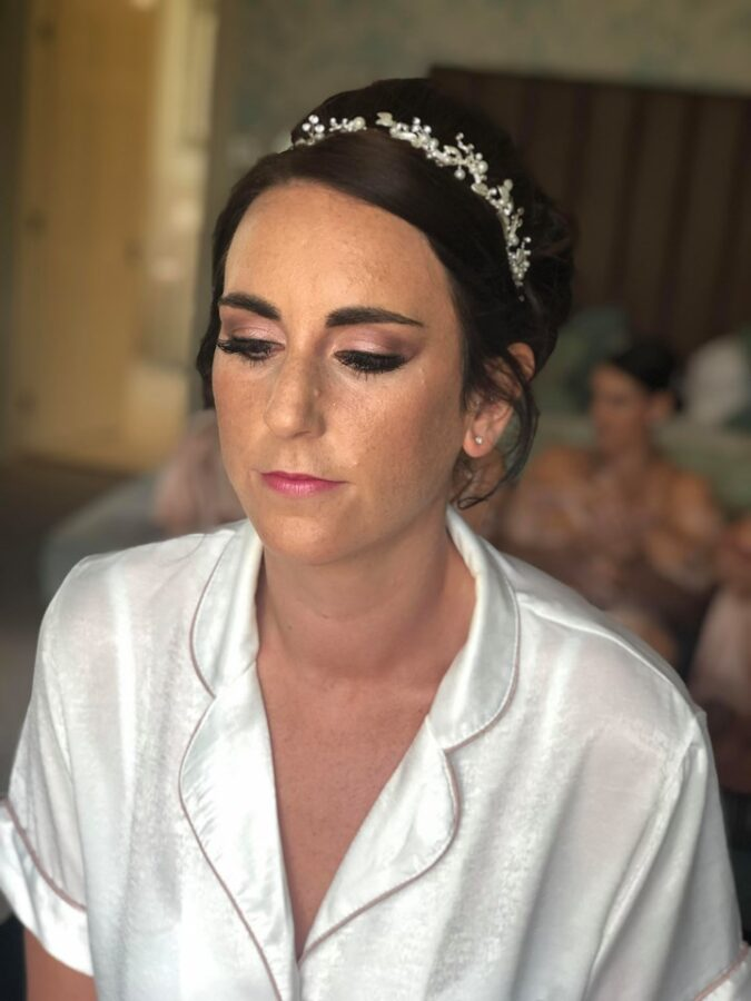 Bridal makeup showing glowing, freckly skin and well maintained brows for wedding at Storrs Hall, the Lakes District.